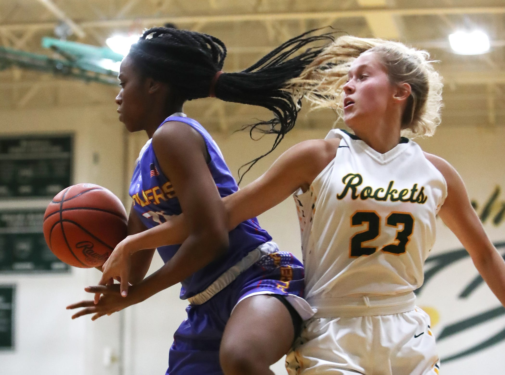 McNicholas forward Christina Poole goes after a rebound against Purcell guard Jaimone Jones. McNicholas upset Purcell 51-50.