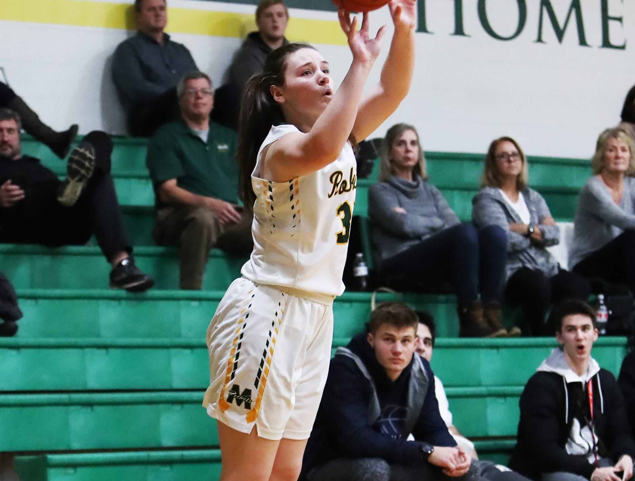 McNicholas forward Maggie Schoolfield attempts a three-point shot. McNicholas upset Purcell 51-50.