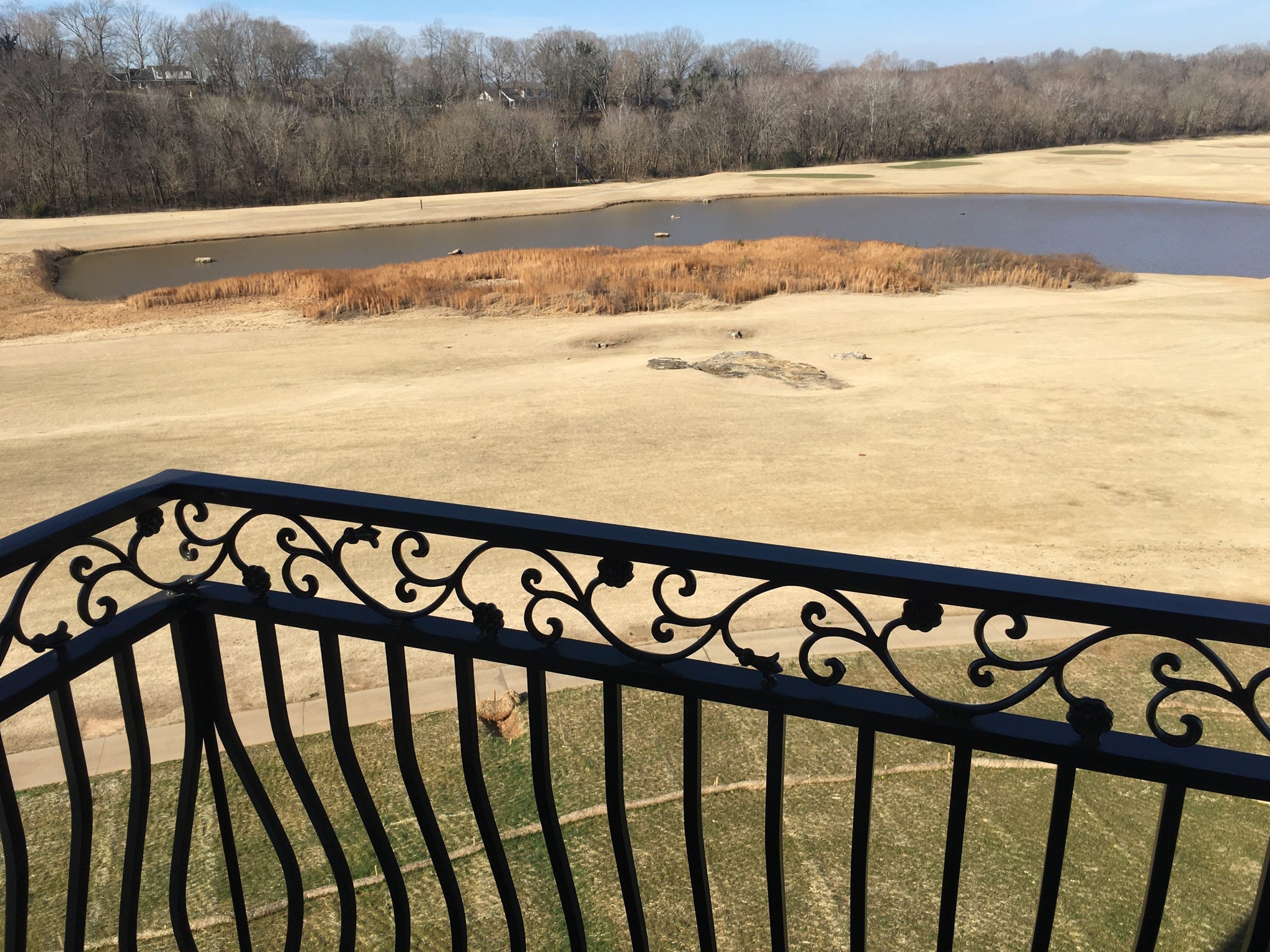 Standing on a pergola balcony   from one of the suites at the Villages at the River Club, overlooking the pond, golf course and woodlands.