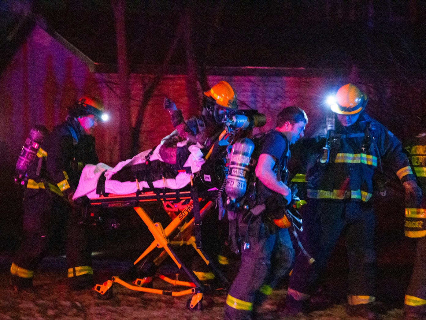 Emergency personnel transport an elderly woman out of a burning house at 1113 37th Street on Wednesday, Jan. 9, 2018.