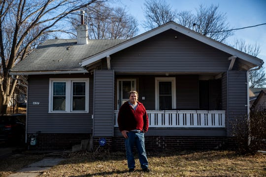 Adam McElhenny stands in front of his home on Thursday, Jan. 10, 2019 on Des Moines' north side. McElhenny's home was damaged by summer flooding and was eligible for purchase by the city, he turned it down and chose to remain there.