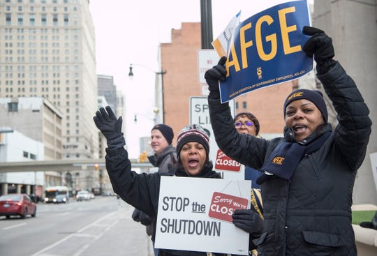 "From left, FDA employee Cheryl Monroe and Social Security Administration employee Monique Buchanan wave at cars on Michigan Avenue and chant ""Let me do my job, open the government now,"" outside of the Patrick V. McNamara Federal Building in Detroit, Thursday, Jan. 10, 2019."