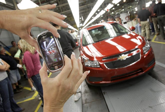 Dealers continue to offer aggressive lease deals on compact cars, such as the Chevrolet Cruze. FILE - In this Sept. 8, 2010 file photo, auto worker Brenda Hedland takes a picture of the first Chevrolet Cruze compact sedan to come off the assembly line at a ceremony inside the GM factory in Lordstown, Ohio.