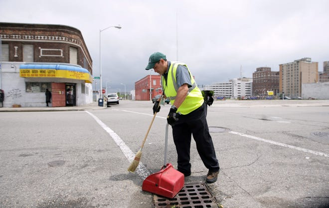 Marc Sandoval of Detroit, who works for Clean Downtown effort, cleans along the streets of Cass and Henry in Detroit on Thursday, July 2, 2009.