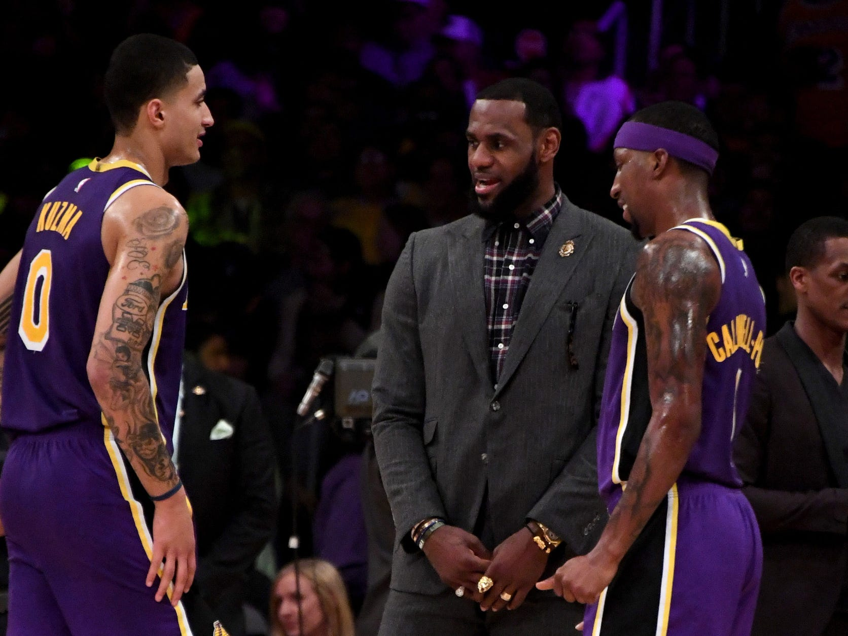 Los Angeles Lakers forward LeBron James (center) talks with forward Kyle Kuzma (left) and guard Kentavious Caldwell-Pope (right) during the first half against the Detroit Pistons at the Staples Center on Wednesday, Jan. 9, 2019, in Los Angeles.