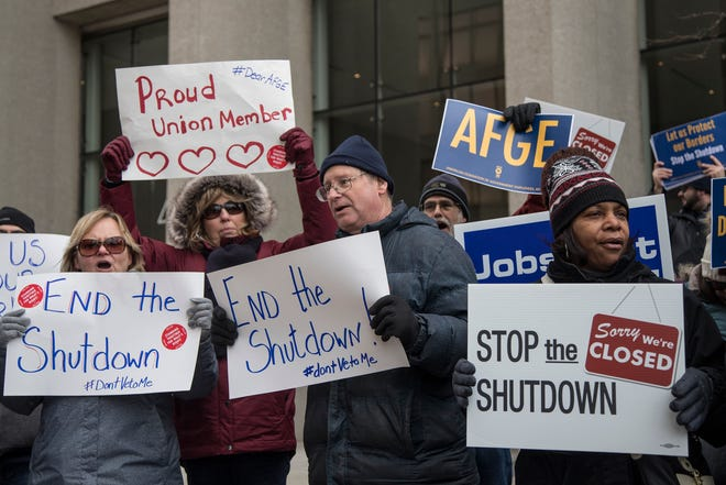 Federal employees with their family and friends protest the government shutdown outside of the Patrick V. McNamara Federal Building in Detroit, Thursday, Jan. 10, 2019.