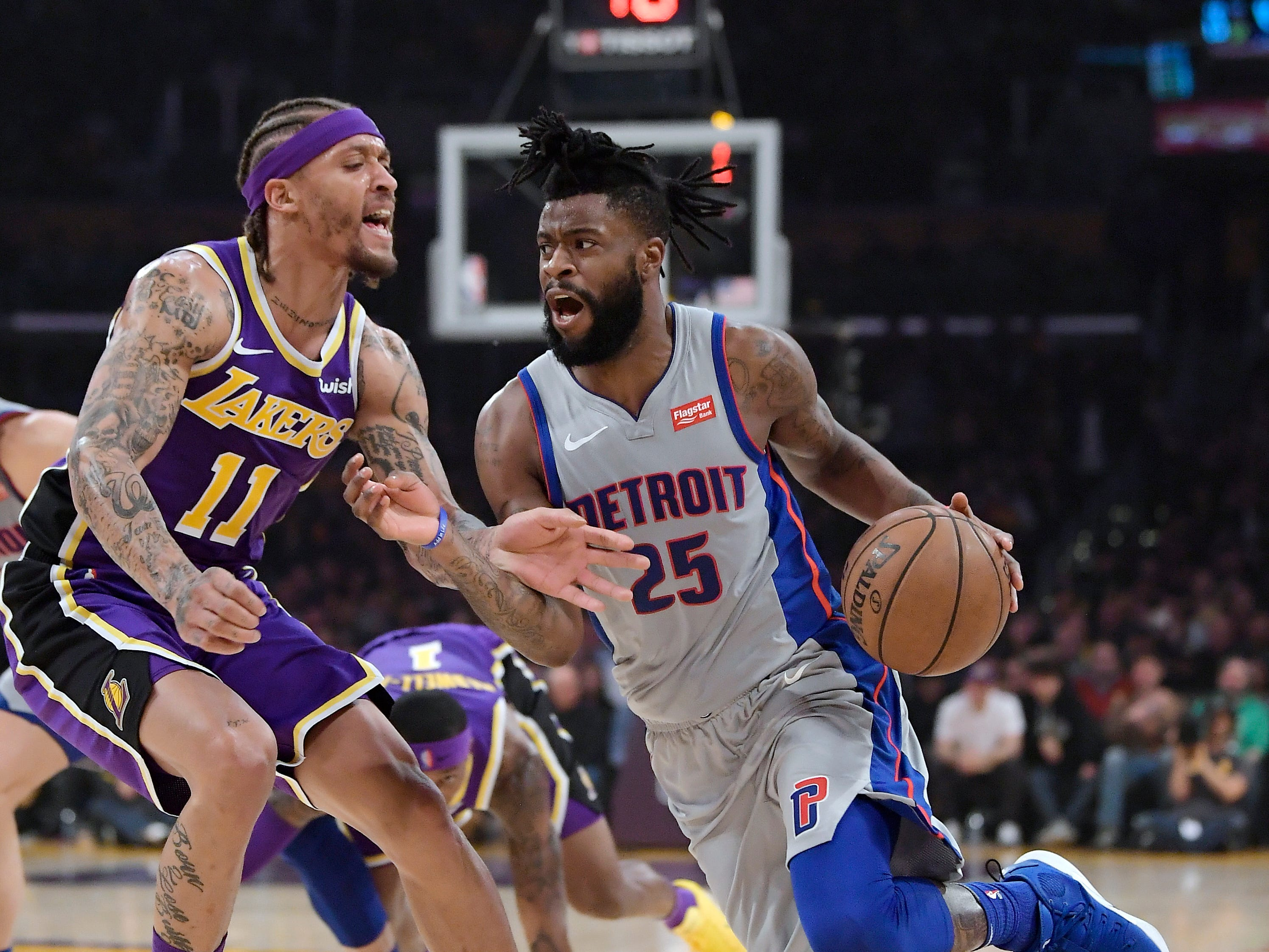 Detroit Pistons guard Reggie Bullock, right, tries to drive past Los Angeles Lakers forward Michael Beasley during the first half of an NBA basketball game Wednesday, Jan. 9, 2019, in Los Angeles.