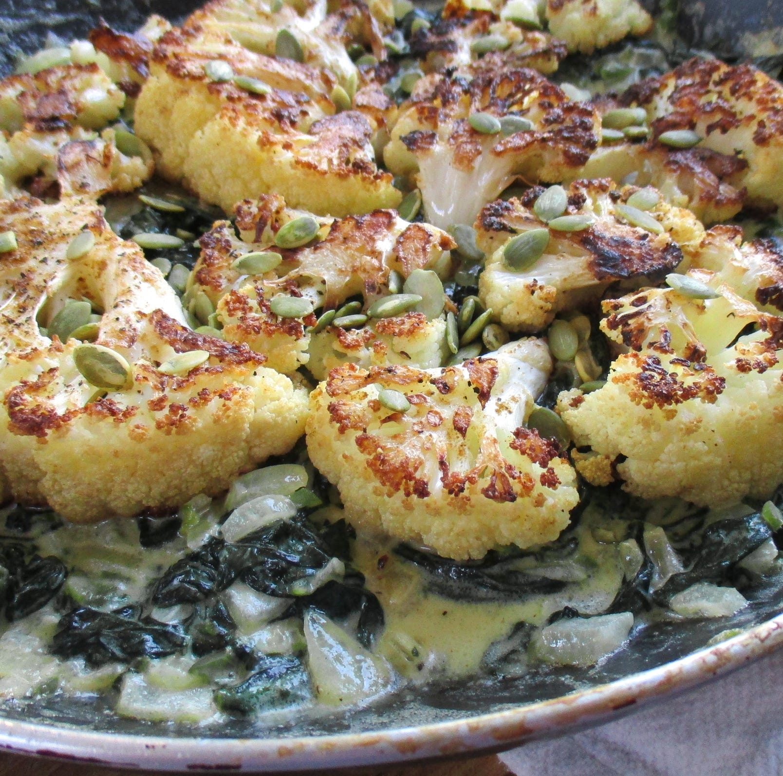 Roasted cauliflower over creamed spinach will delight keto dieters