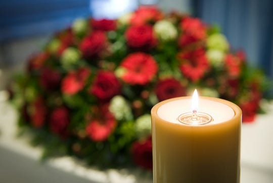 A burning candle with a white coffin and a flower arrangement on the background