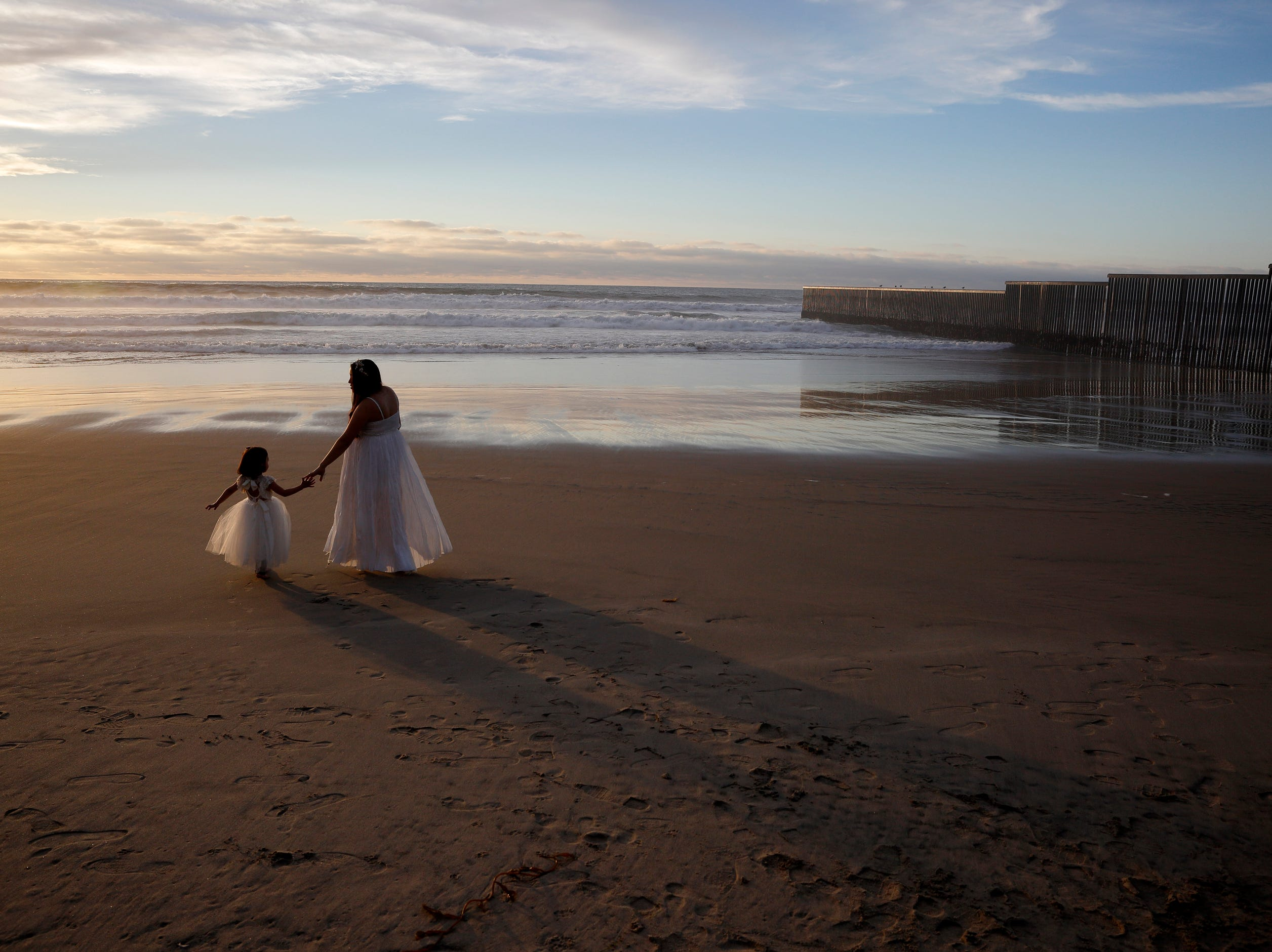 Ileze Dariel, of Tijuana, Mexico, reaches for the hand of her daughter, Jimena, as they wait for a photographer on the beach next to the border wall, right, Wednesday, Jan. 9, 2019, in Tijuana, Mexico.
