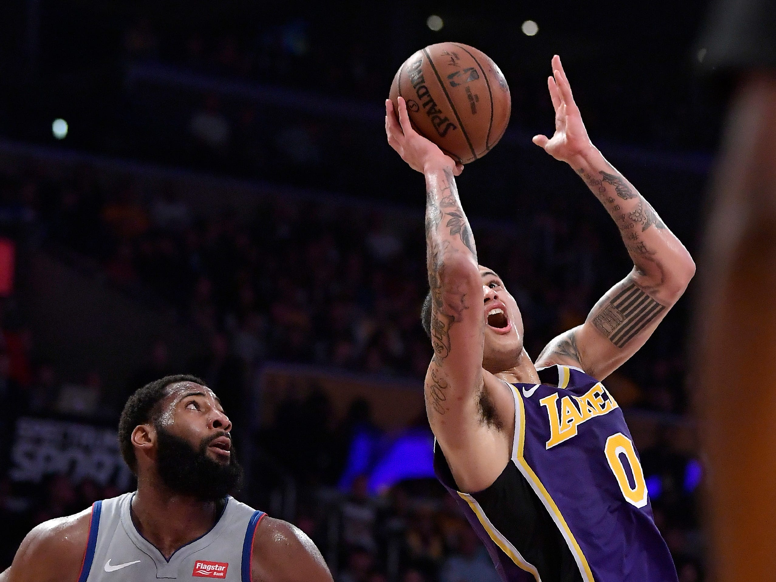 Los Angeles Lakers forward Kyle Kuzma, right, shoots as Detroit Pistons center Andre Drummond defends during the second half.
