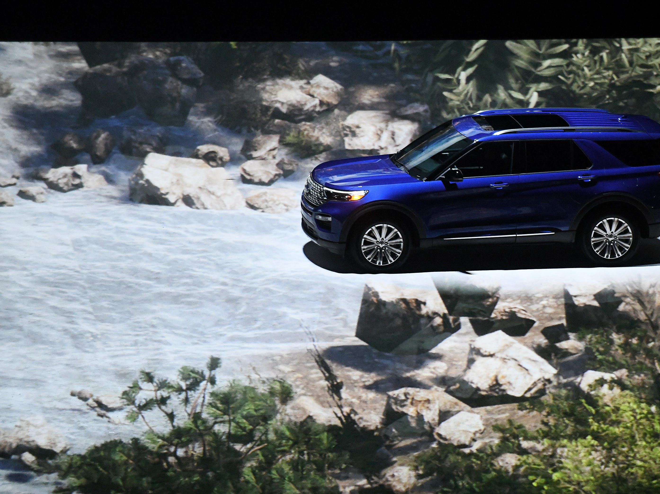 A 2020 Ford Explorer appears to be driving through the Rocky Mountains due to video effects.