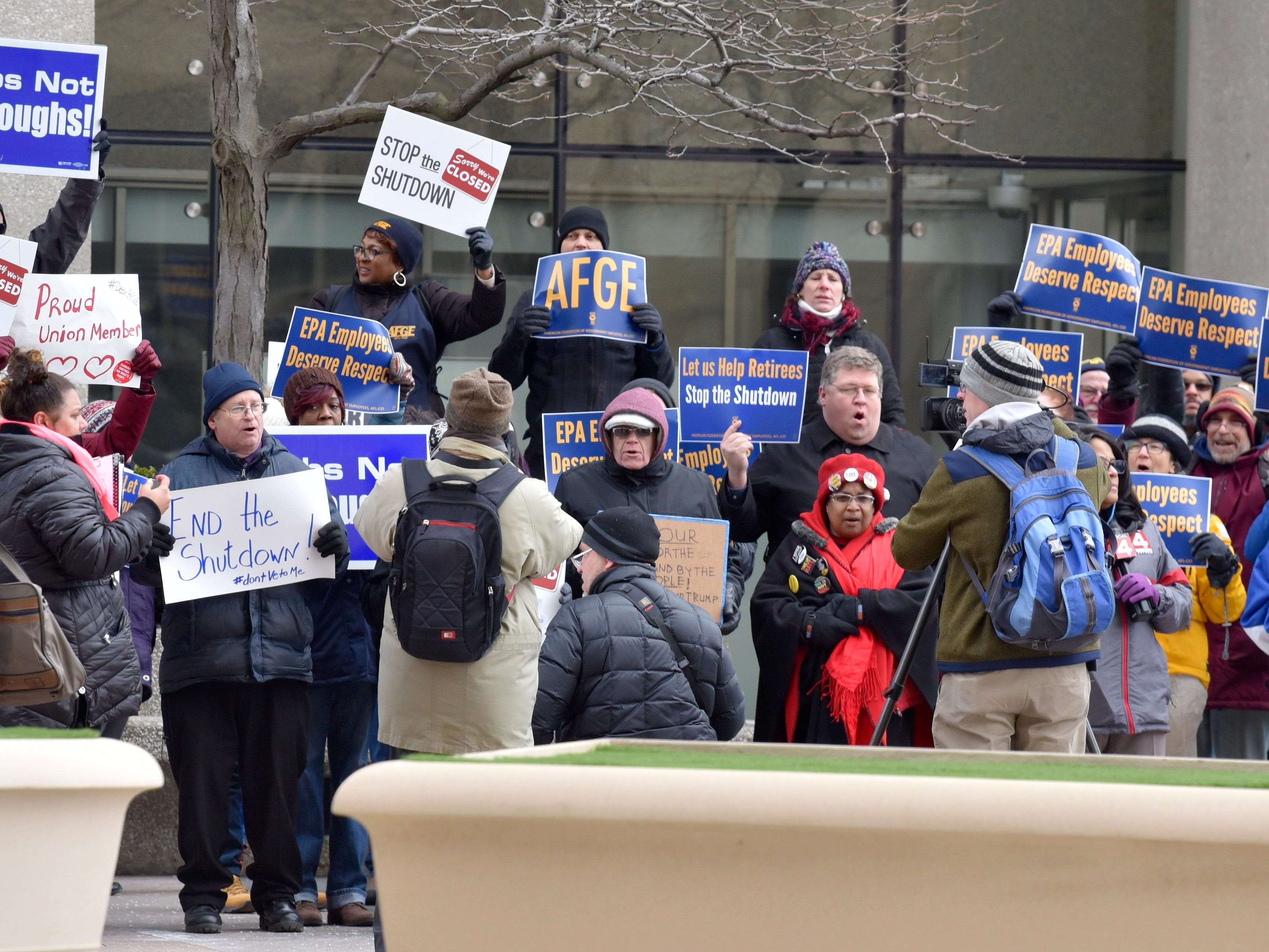Government employees protest in front of Patrick V. McNamara Federal Building, Thursday afternoon.