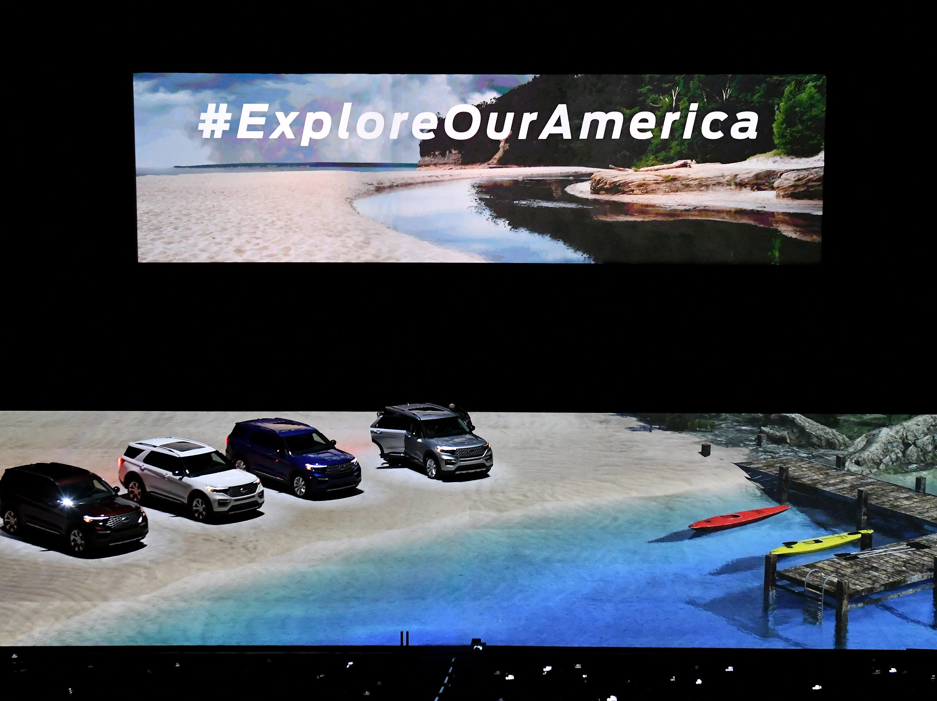 2020 Ford Explorers appears to be driving on a beach due to video effects projected on the floor of Ford Field.