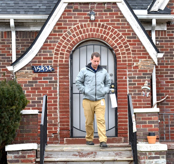 City of Detroit Building Inspector Ken Potenga walks off the porch of a Detroit house after retrieving information on the rental-ordinance-related ticket he securely taped to the front door of this property.