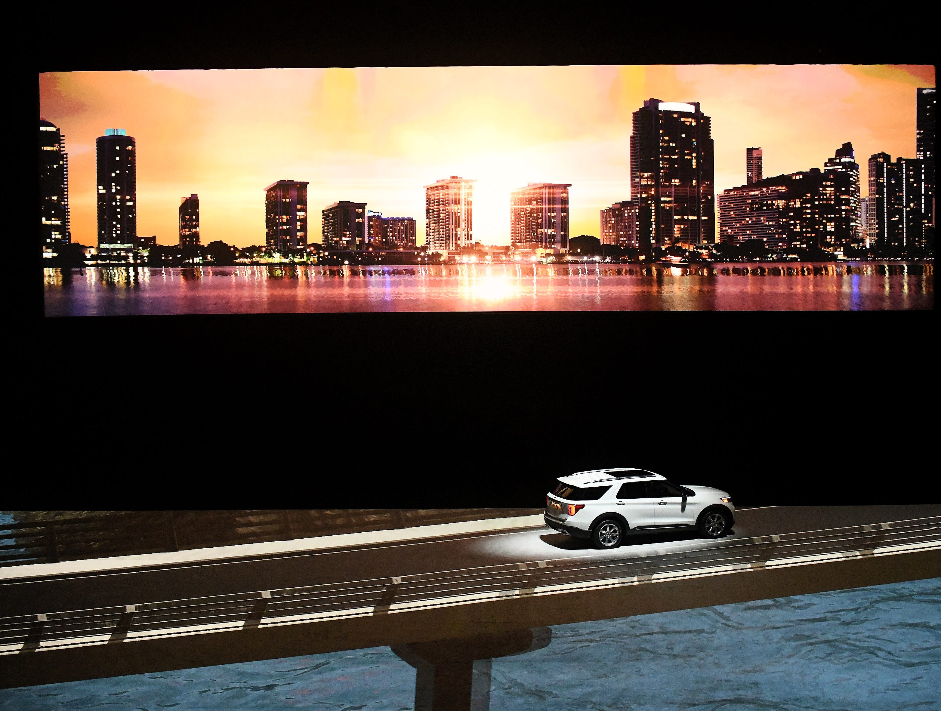A 2020 Ford Explorer appears to be driving on a bridge over water due to video effects projected on the floor of Ford Field.