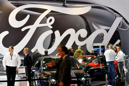 Visitors are seen at the stand of car maker Ford during the 'Essen Motor Show' fair in Essen, western Germany, on December 1, 2017.)