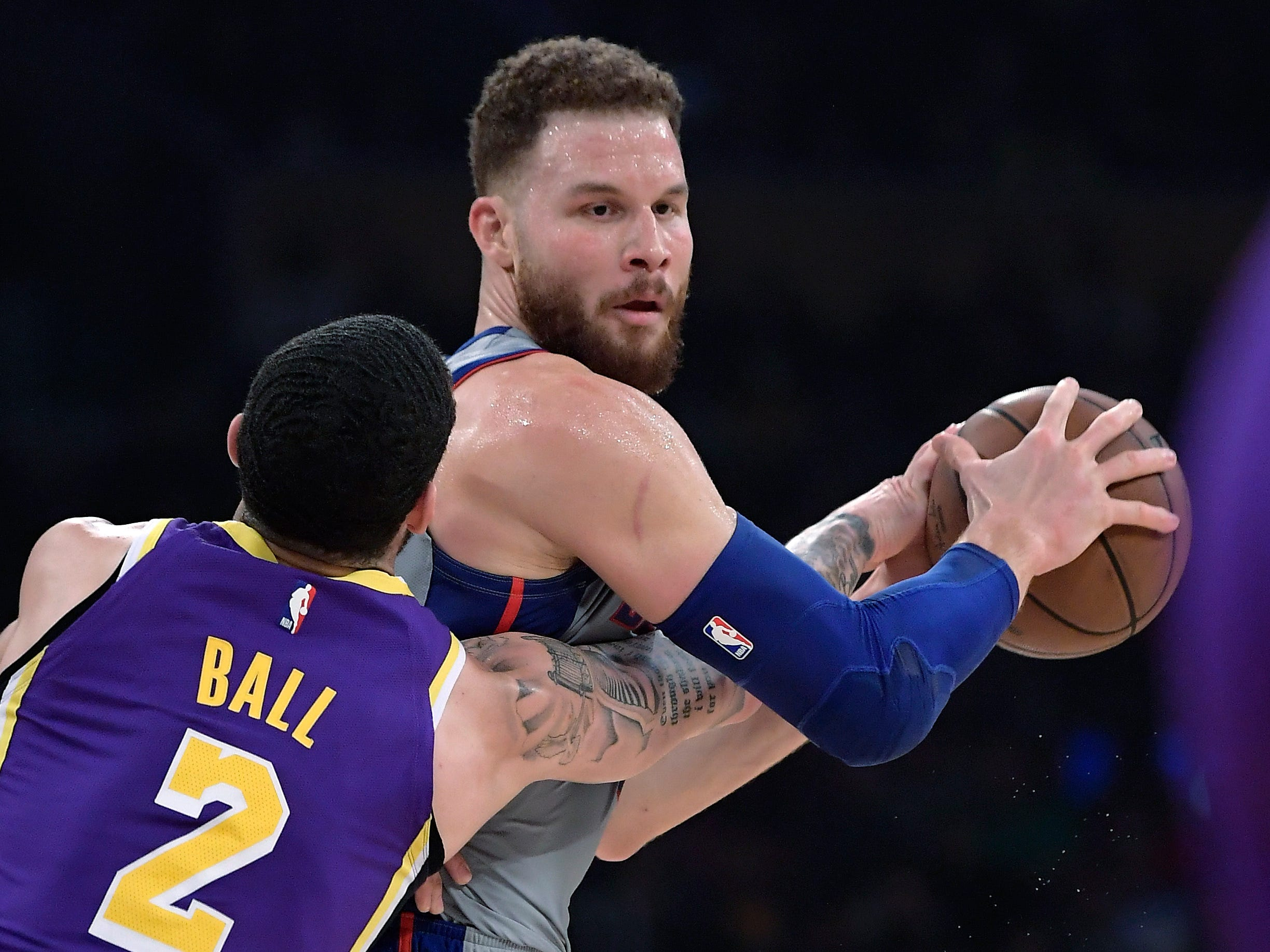 Los Angeles Lakers guard Lonzo Ball, left, reaches for the ball held by Detroit Pistons forward Blake Griffin during the first half.