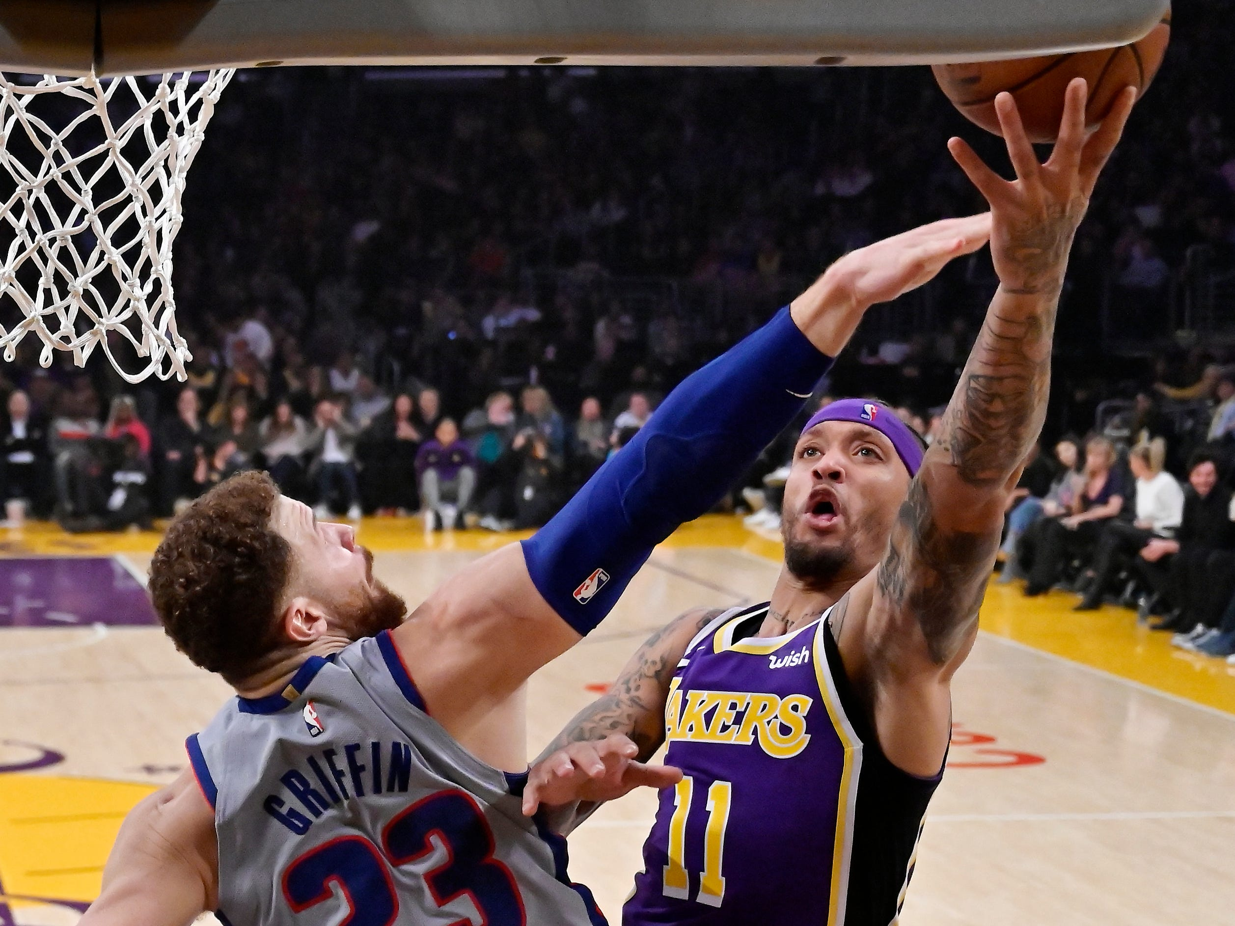 Los Angeles Lakers forward Michael Beasley, right, shoots as Detroit Pistons forward Blake Griffin defends during the first half.