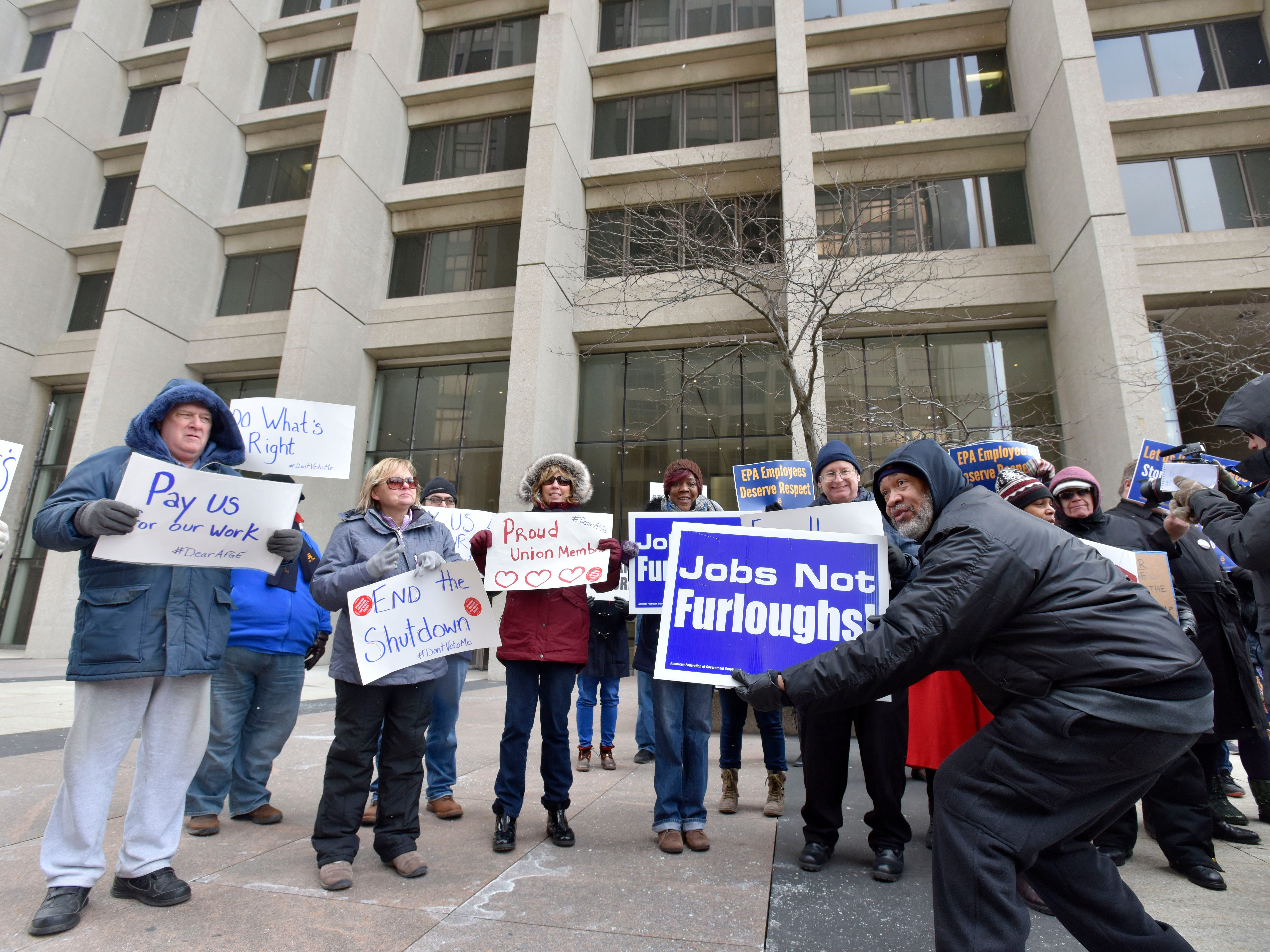 TSA Officer Gregory Simpkins, right, holds up his sign with other protesters. He is the president of Local 778 representing Michigan TSA officers. Federal employees protest the partial government shutdown in front of the Patrick V. McNamara Federal Building in Detroit, Thursday afternoon, January 10, 2019.