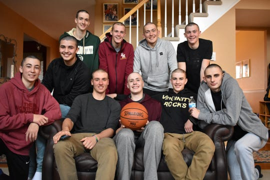 Rocky Mountain basketball players pose for a photo after shaving their heads in support of teammate Carter Edgerely, with ball, who is battling bone cancer. Players from front left are Joseph Naddy, Jaeden Lucero,  Joseph Urynowicz, Edgerely, Leo Von Bargen and Tyler Fisher. Back row from left are Gilon Dierks, Kenan Schuler, Peter Krohn and Dawson Otto.