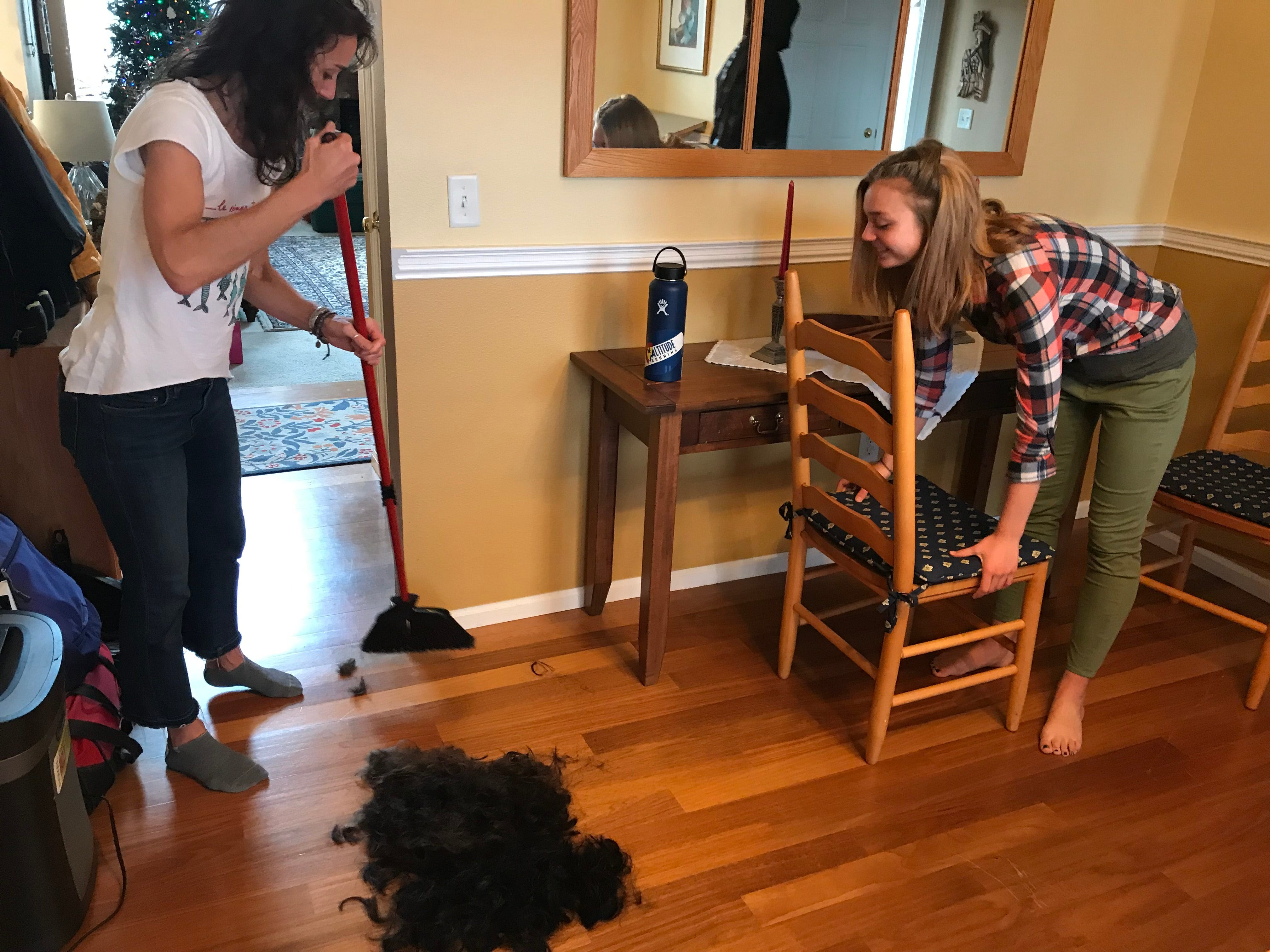 Margaret Urynowicz sweeps up hair from the shaved heads of Rocky Mountain basketball players as daughter Elizabeth looks on.