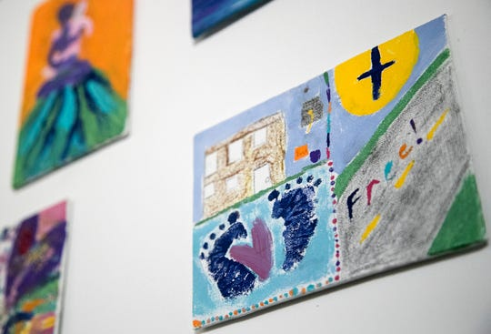 Paintings done by women in the support group run by Into the Jordan Ministries hang on the wall in the children's area. The women can come to the group and get support and also food, toiletries, services and exercise.