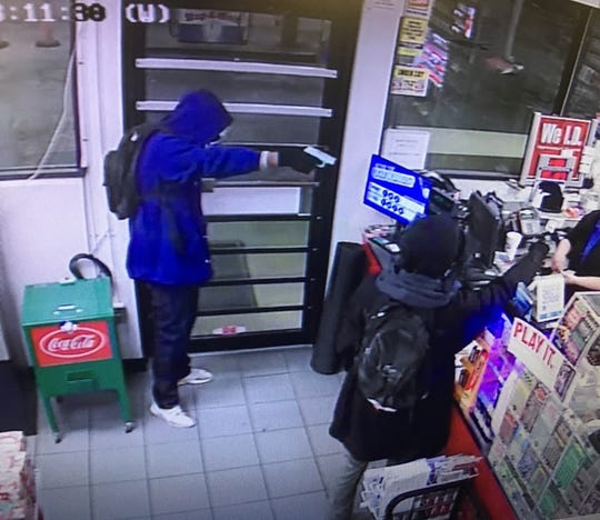 Two teenagers point guns and demand money from cashier.