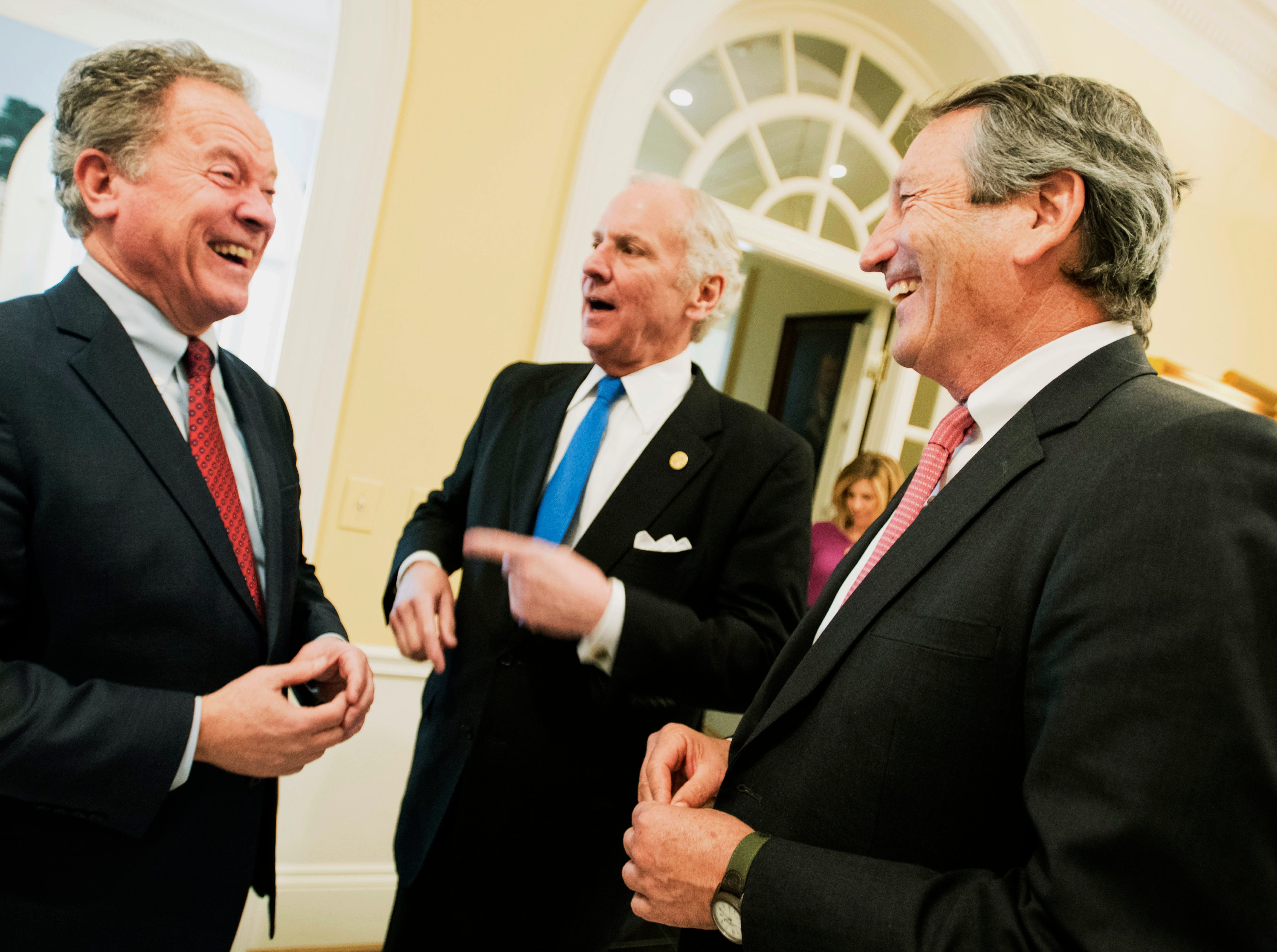 Former South Carolina Governors Mark Sanford, right, and David Beasley, left, joke around with current governor Henry McMaster at the South Carolina Governor's Mansion, Wednesday, Jan. 9, 2019, in Columbia, S.C. McMaster was inaugurated for his first full term earlier in the day. (AP Photo/Sean Rayford)