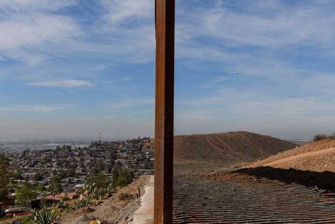 FILE - This Saturday, Dec. 22, 2018 file photo shows Tijuana, Mexico, left, and San Diego, Calif., separated by a U.S. border fence. The partial government shutdown which started in December 2018 has furloughed hundreds of thousands of government employees and halted services that aren't deemed essential, including, in many instances, the immigration courts overseen by the Justice Department. (AP Photo/Daniel Ochoa de Olza)