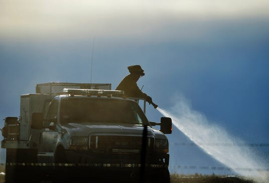Volunteer firefighters put out hot spots from a grass fire on Cottonwood Coulee Road outside of Stockett in 2019.