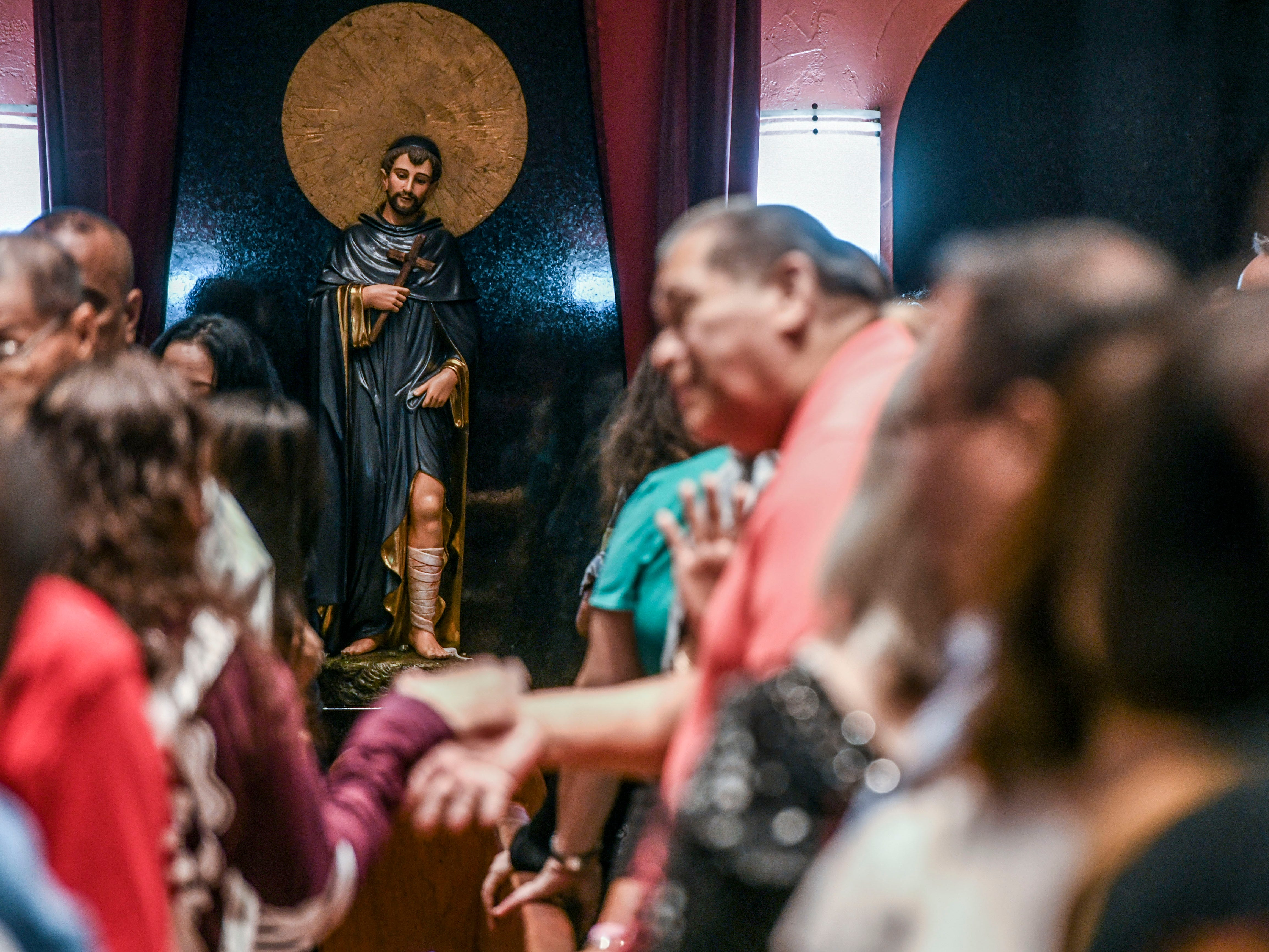 A statue of St. Peregrine looks down on parishioners as they offer each other a sign of peace during the inaugural devotion Mass to St. Peregrine at the Dulce Nombre de Maria Cathedral-Basilica in Hagåtña on Wednesday, Jan. 9, 2019. An unveiling, blessing and enthronement for the was held during the Mass. The Archdiocese of Agaña announced that Mass will be offered at 6:00 p.m. on Wednesdays for cancer patients, their families and all who would like to participate in celebration of the Eucharist and prayers. Confession will also be offered before each Mass, as well as an anointing of the sick, said Monsignor James Benavente, pastor of the Cathedral-Basilica.