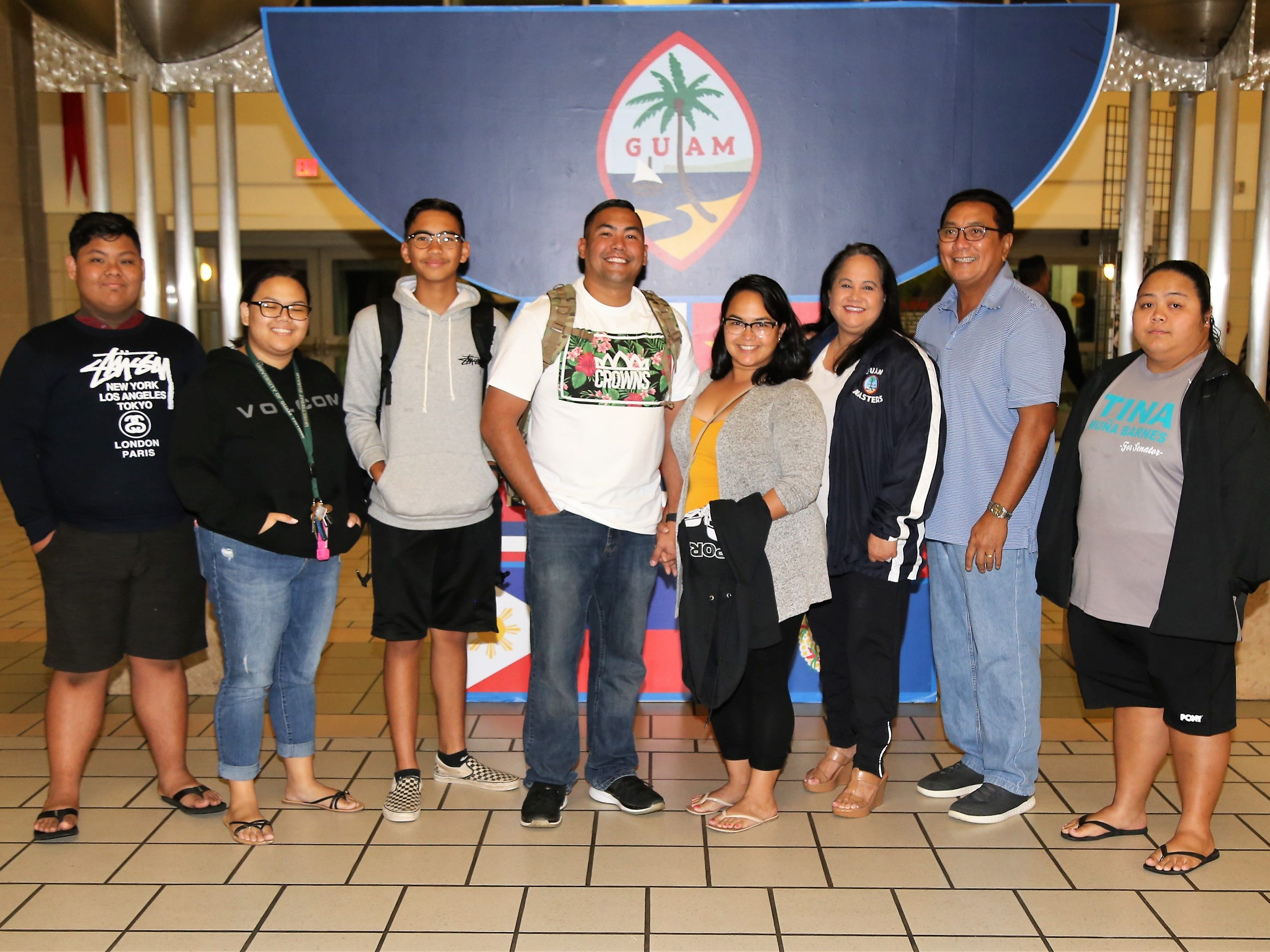 Technical Sgt. Jacob Barnes, from the Guam Air National Guard's 254th Air Base Group's Cyber Flight, at center in white, poses for a photo with family members at the Guam International Airport Authority.