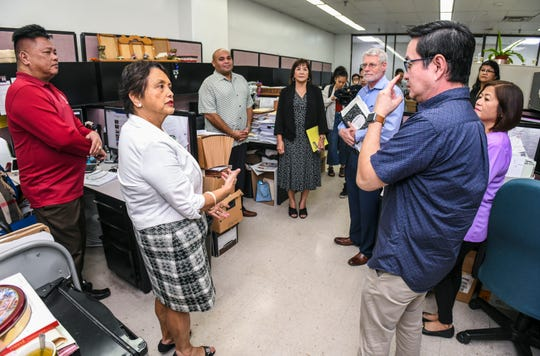 Gov. Lou Leon Guerrero, front left, converses with Chief Payroll Officer Gil Galang as she, Lt. Gov. Josh Tenorio and others visit the Payroll Branch of the Department of Administration in Tamuning on Wednesday, Jan. 10, 2019.