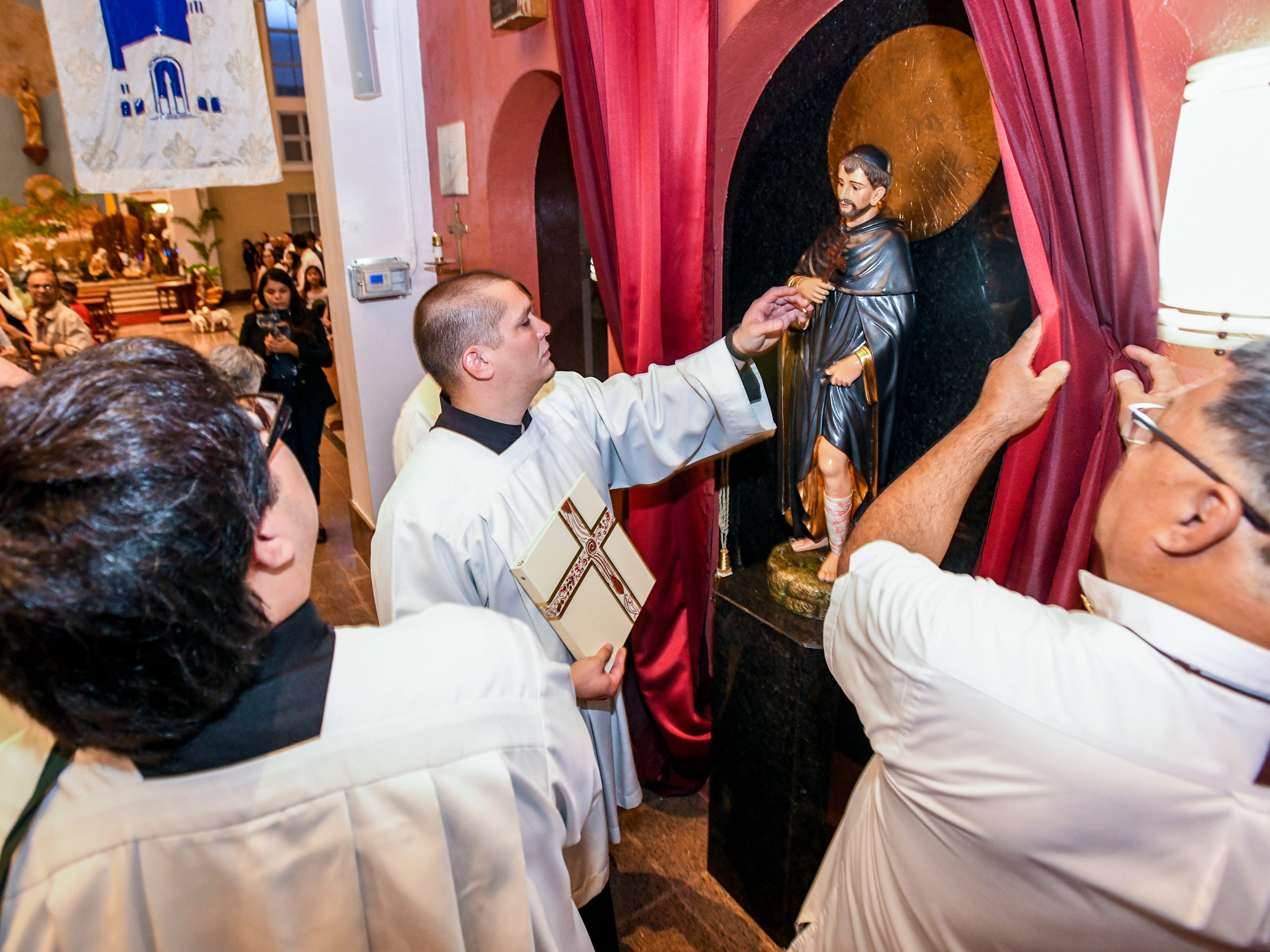 Curtains are pulled back to reveal the newly enthroned statue of St. Peregrine during the inaugural devotion Mass to the saint at the Dulce Nombre de Maria Cathedral-Basilica in Hagåtña on Wednesday, Jan. 9, 2019. The Archdiocese of Agaña announced that Mass will be at 6:00 p.m. on Wednesdays for cancer patients, their families and all who would like to participate in celebration of the Eucharist and prayers. Confession will also be offered before each Mass, as well as an anointing of the sick, said Monsignor James Benavente, pastor of the Cathedral-Basilica.