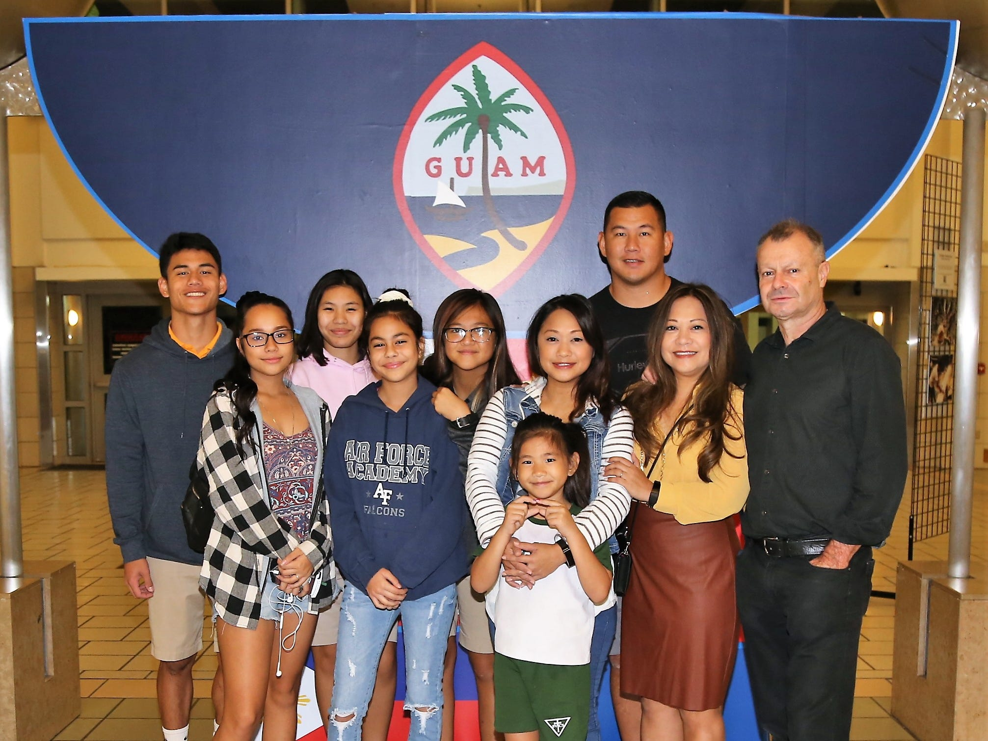 Technical Sgt. Michelle Castro, from the Guam Air National Guard's 254th Air Base Group's Cyber Flight, at center in stripes, poses for a photo with family members at the Guam International Airport Authority last week, just prior to departing for a deployment in support of Operation Inherent Resolve in Southwest Asia.
