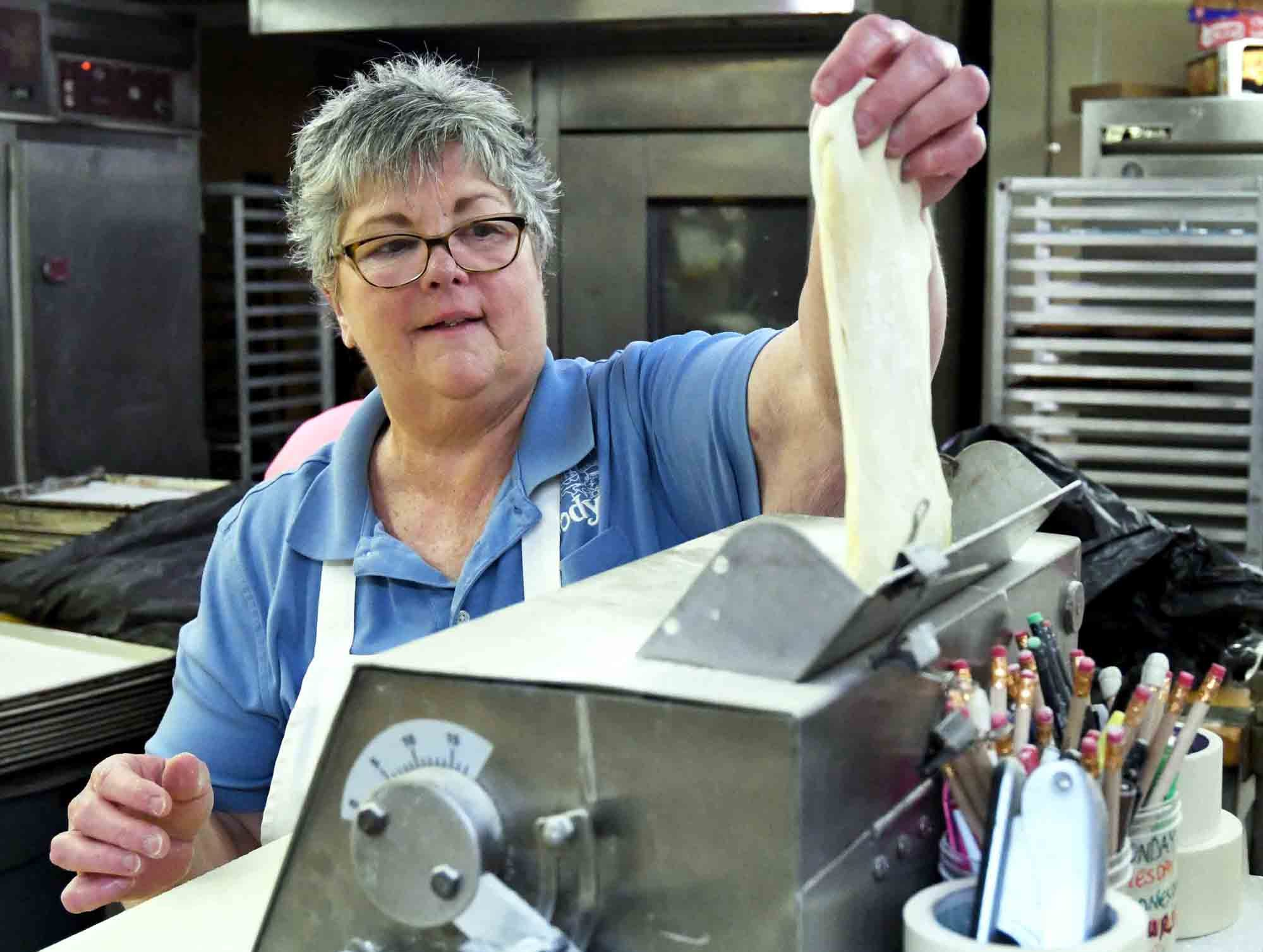 Jody Lopez places dough in a machine to flatten out as Jody's Bakery prepares to make king cakes in Hattiesburg.