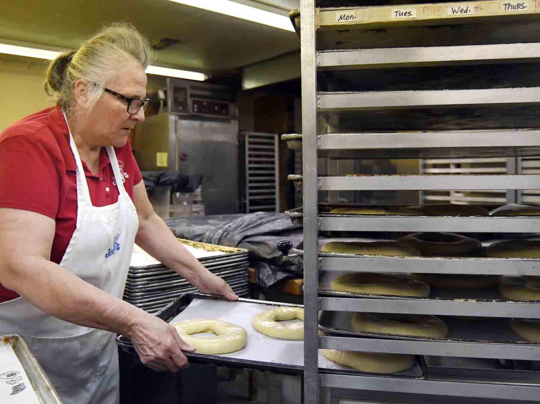 Shirley Nichols places a tray of dough to the rack for baking  as Jody's Bakery prepares to make king cakes in Hattiesburg.
