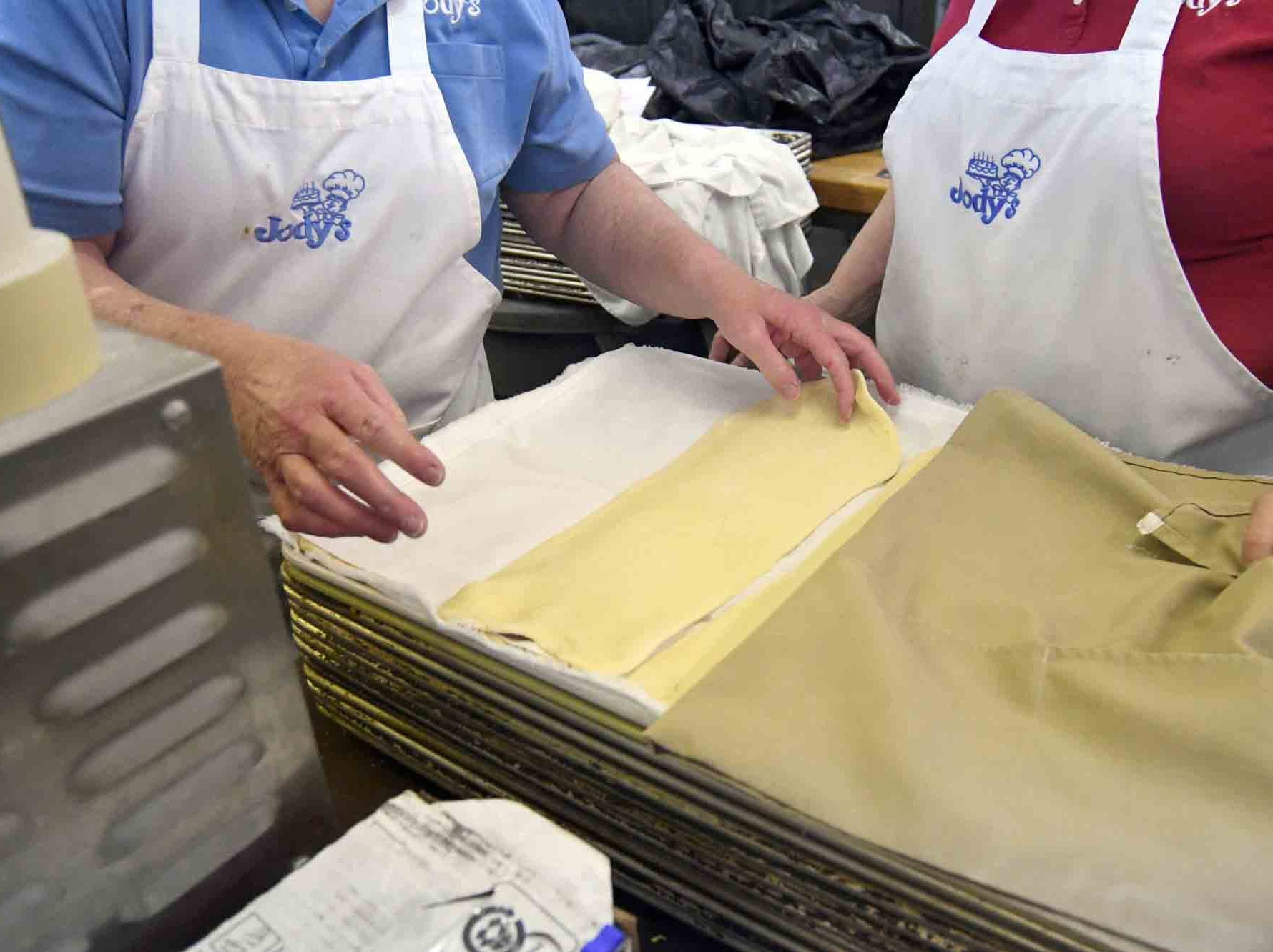 Flatten dough is placed on a tray to be placed in the freezer as Jody's Bakery prepares to make king cakes in Hattiesburg.