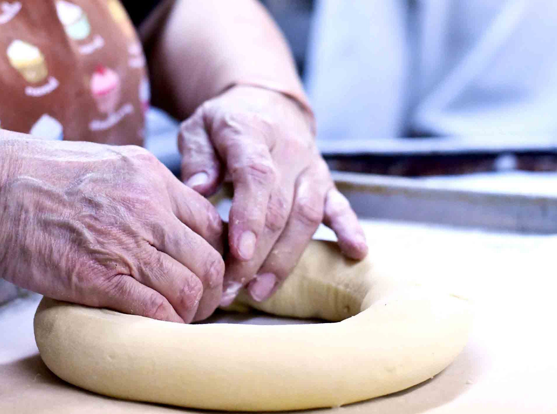 Jade Rock forms dough together as Jody's Bakery prepares to make king cakes in Hattiesburg.