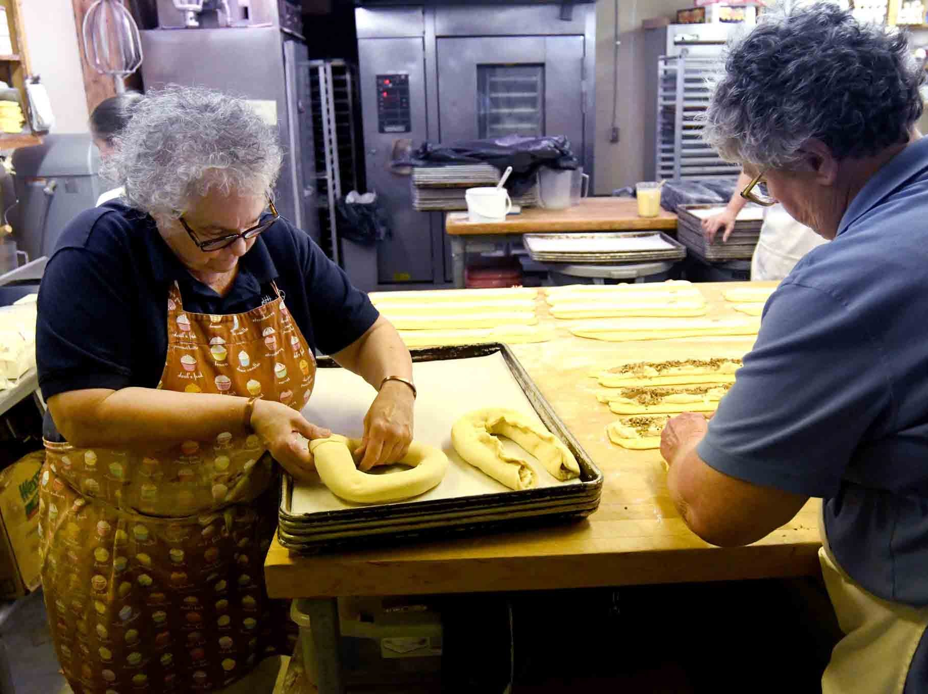 Jade Rock, left, and Jody Lopez, right, form the filled dough as Jody's Bakery prepares to make king cakes in Hattiesburg.