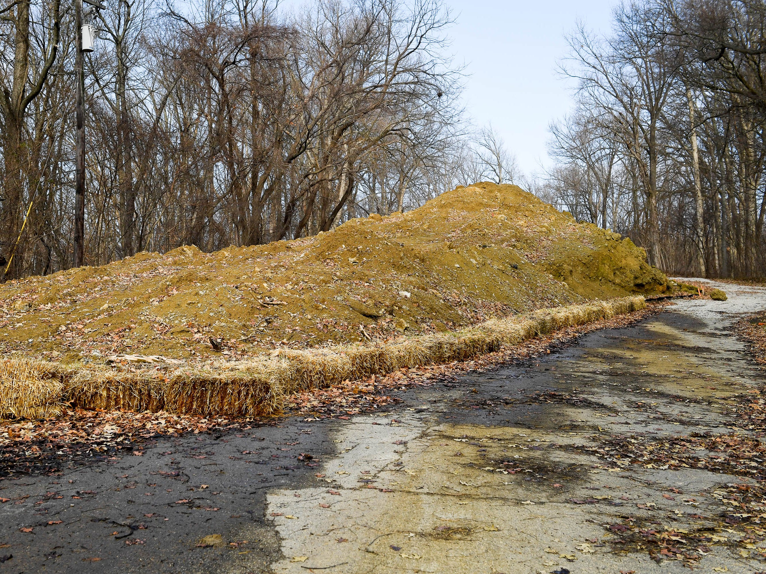 Soil to be used to rebuild the levee at Audubon State Park's Scenic Lake is piled up on the parking lot above the lake Thursday, January 3, 2019.