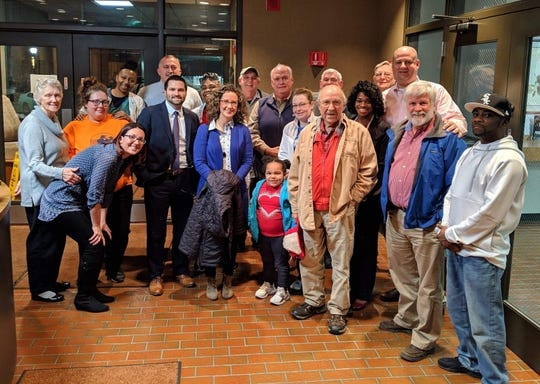 Britney Smith, second from left, poses with a big group of Habitat for Humanity families, staffers and volunteers who came to the Henderson City Commission meeting Tuesday evening to support a proposal for the city and Habitat to team up on an East End Redevelopment project.