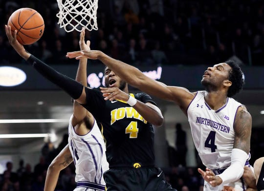Iowa guard Isaiah Moss drives to the basket against Northwestern forward Vic Law (right) and guard Ryan Taylor during the first half Wednesday in Evanston, Ill.