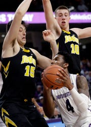 Northwestern forward Vic Law (4) drives to the basket as Iowa forward Ryan Kriener, left, and guard Joe Wieskamp guard during the second half of an NCAA college basketball game Wednesday, Jan. 9, 2019, in Evanston, Ill. Iowa won 73-63. (AP Photo/Nam Y. Huh)