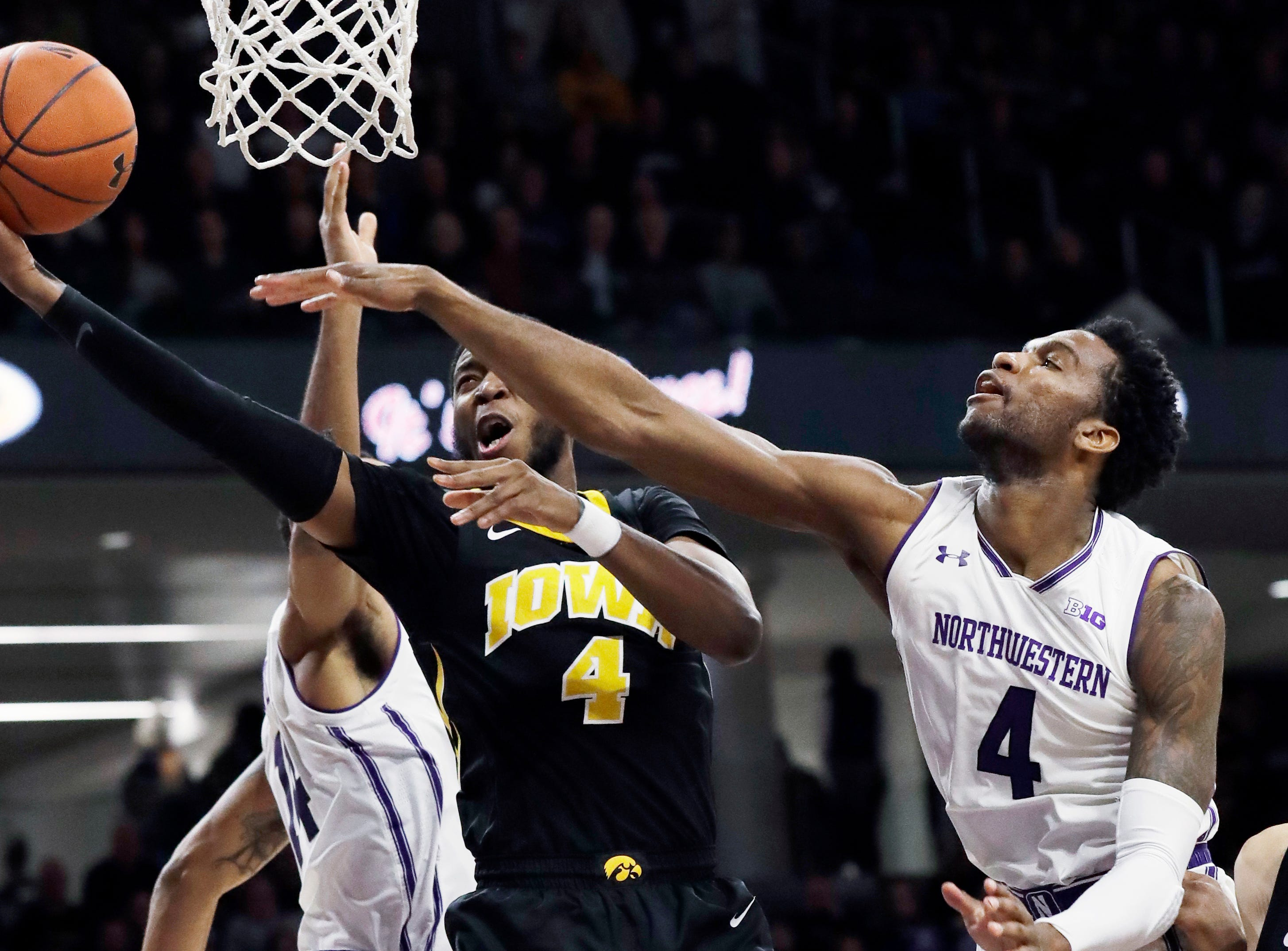 Iowa guard Isaiah Moss, left, drives to the basket against Northwestern forward Vic Law, right, and guard Ryan Taylor during the first half of an NCAA college basketball game Wednesday, Jan. 9, 2019, in Evanston, Ill. (AP Photo/Nam Y. Huh)