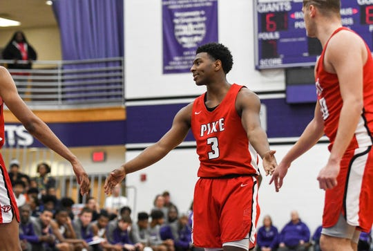 Pike Red Devils guard AJ White (3) taps hands with teammates after scoring a free throw during the second half of Marion County quarterfinals Wednesday at Ben Davis High School in Indianapolis. Pike won, 78-67.