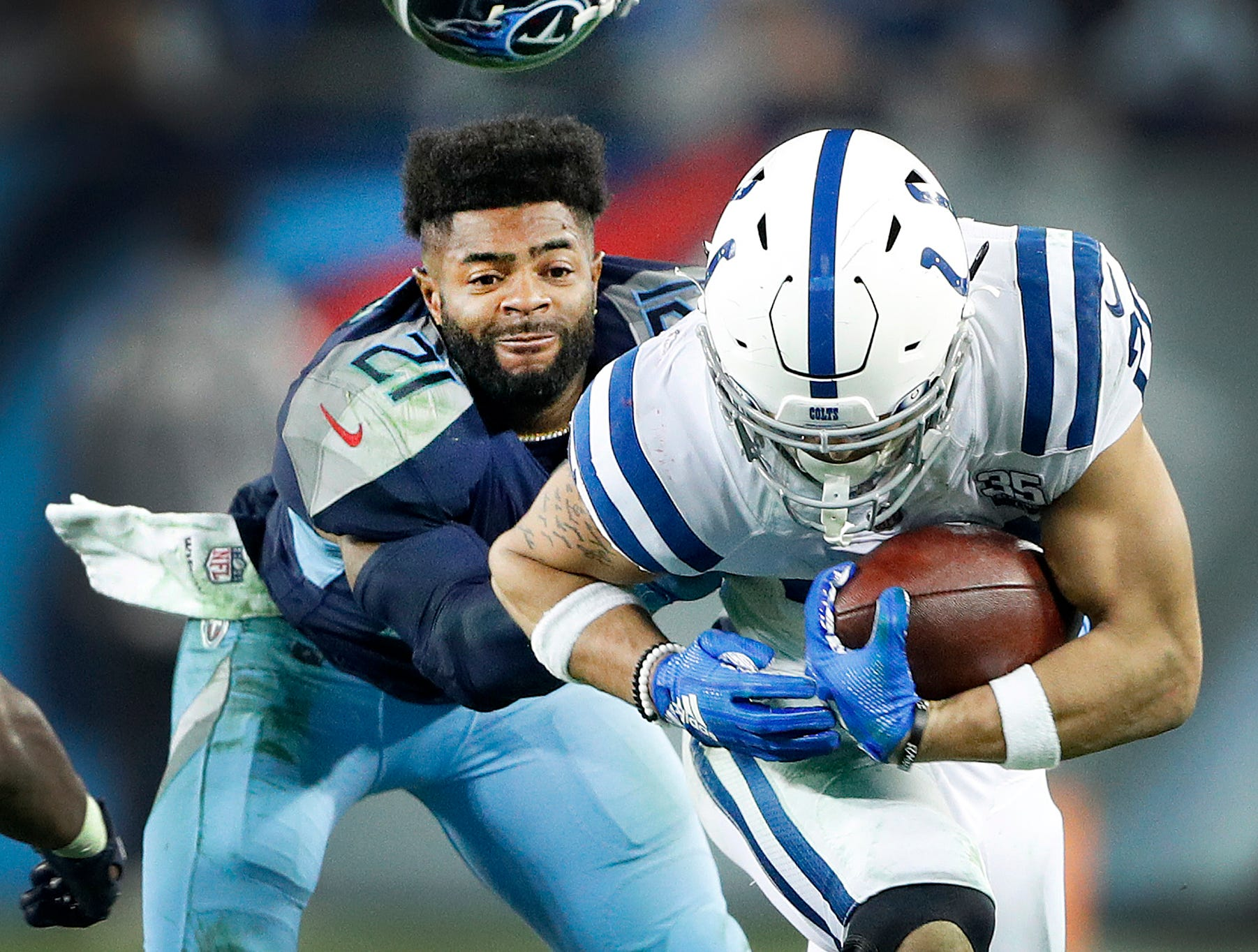 Tennessee Titans cornerback Malcolm Butler (21) loses his hemet as he tries to tackle Indianapolis Colts running back Jordan Wilkins (20) in the fourth quarter of their game against at Nissan Stadium in Nashville, Tenn., on Sunday, Dec. 30, 2018.