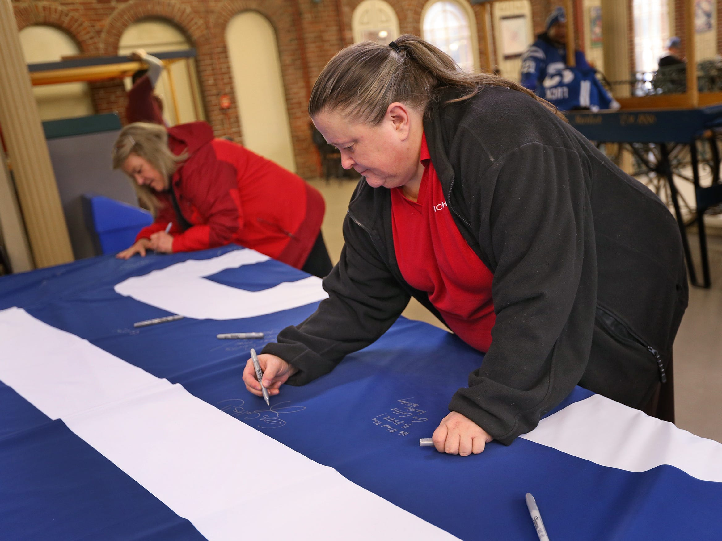 Alicia Scramlin, left, and Lynn Moeller sign a 1-0 banner for the Colts at City Market, Thursday, Jan. 10, 2019.  The banner will be displayed for the team to see at the airport as they head off to their Kansas City playoff game.