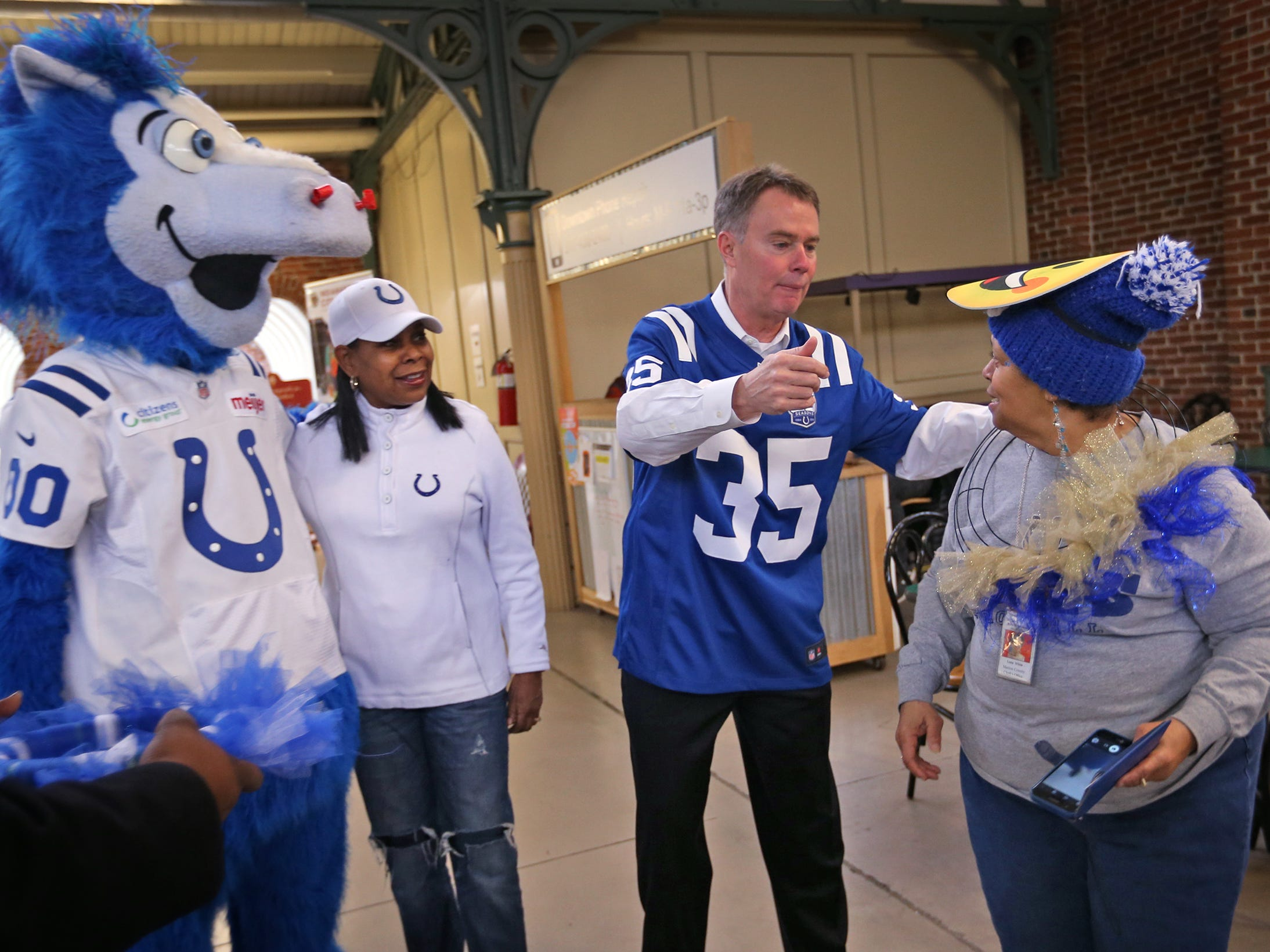 Lonna White, right, gets a hug from Mayor Joe Hogsett as Colts mascot Blue, and Cheryl McClendon look on. Fans had the opportunity to sign a 1-0 banner for the Colts at City Market, Thursday, Jan. 10, 2019.  The banner will be displayed for the team to see at the airport as they head off to their Kansas City playoff game.